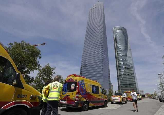 Ambulances wait outside the Torrespacio skyscraper, right, as a jogger runs by in Madrid, Spain, Tuesday, April 16, 2019, after the 57-storey office tower in Madrid's business district that houses several foreign embassies was evacuated due to an unspecified security threat