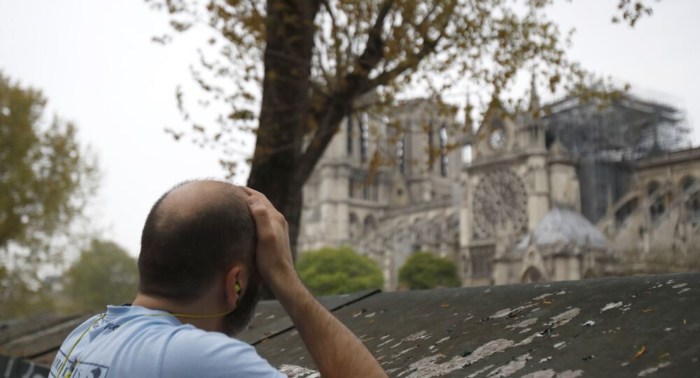 Man holds his head while watching the Notre Dame cathedral after the fire in Paris, Tuesday, April 16, 2019