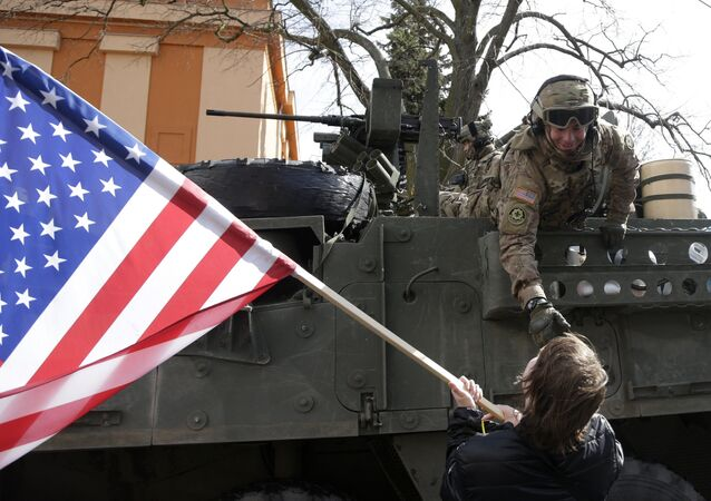 A US army soldier greets a supporter as a US army convoy arrives in Prague, Czech Republic, Monday, March 30, 2015.