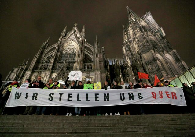 Protestors against KOGIDA stand with banners in front of the Cologne Cathedral during a KOGIDA demonstration rally in Cologne January 21, 2015