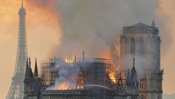 In this image made available on Tuesday April 16, 2019 flames and smoke rise from the blaze after the spire toppled over on Notre Dame cathedral in Paris, Monday, April 15, 2019 - Sputnik International