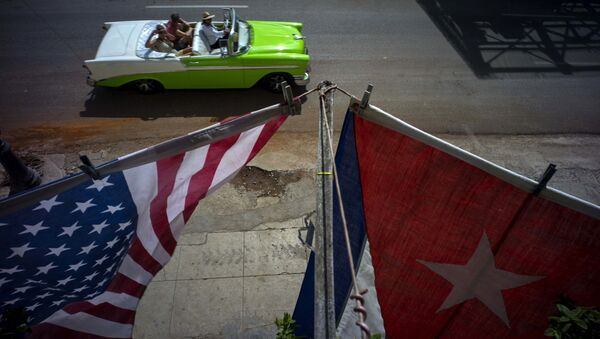 A U.S., and a Cuban national flag, hang from a balcony to mark the restored full diplomatic relations between Cuba and the Unites States, in Old Havana, Monday, July 20, 2015 - Sputnik International