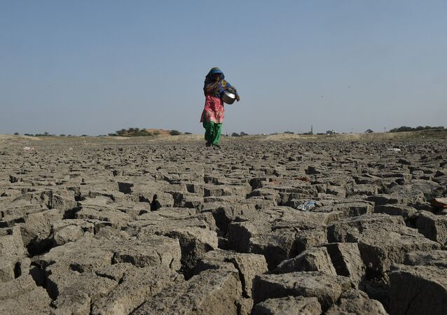 An Indian woman walks over the parched bed of Chandola Lake in Ahmedabad on March 22, 2019, on World Water Day