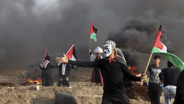 Protesters wave their national flags while others burn tires near the fence of Gaza Strip border with Israel during a protest east of Gaza City, Friday, Nov. 9, 2018 - Sputnik International