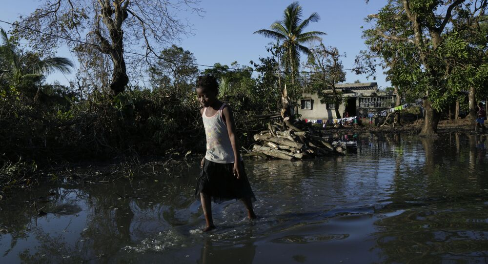 a young girl walks through flood waters near Beira, Mozambique, March 26, 2019, in one of the world's areas most vulnerable to global warming's rising waters
