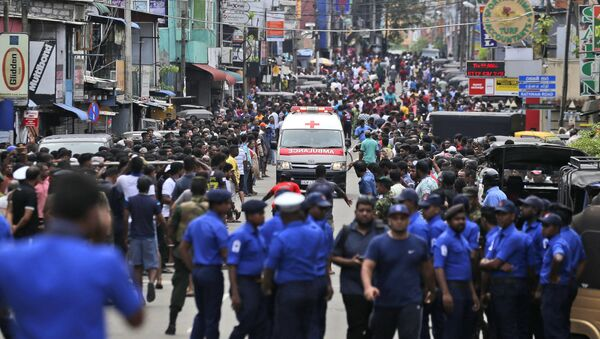 Sri Lankan police officers clear the road as an ambulance drives through carrying injured of Church blasts in Colombo, Sri Lanka, Sunday, April 21, 2019. A Sri Lanka hospital spokesman says several blasts on Easter Sunday have killed dozens of people. - Sputnik International