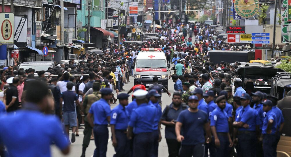 Sri Lankan police officers clear the road as an ambulance drives through carrying injured of Church blasts in Colombo, Sri Lanka, Sunday, April 21, 2019. A Sri Lanka hospital spokesman says several blasts on Easter Sunday have killed dozens of people.