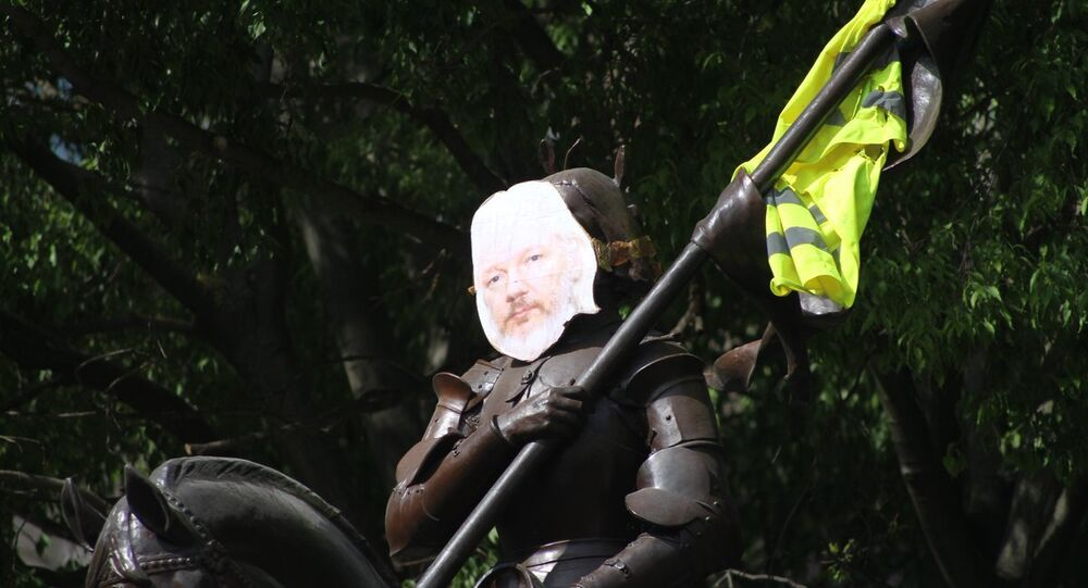 Julian Assange's photo attached to the statue of Joan of Arc in Toulouse, France