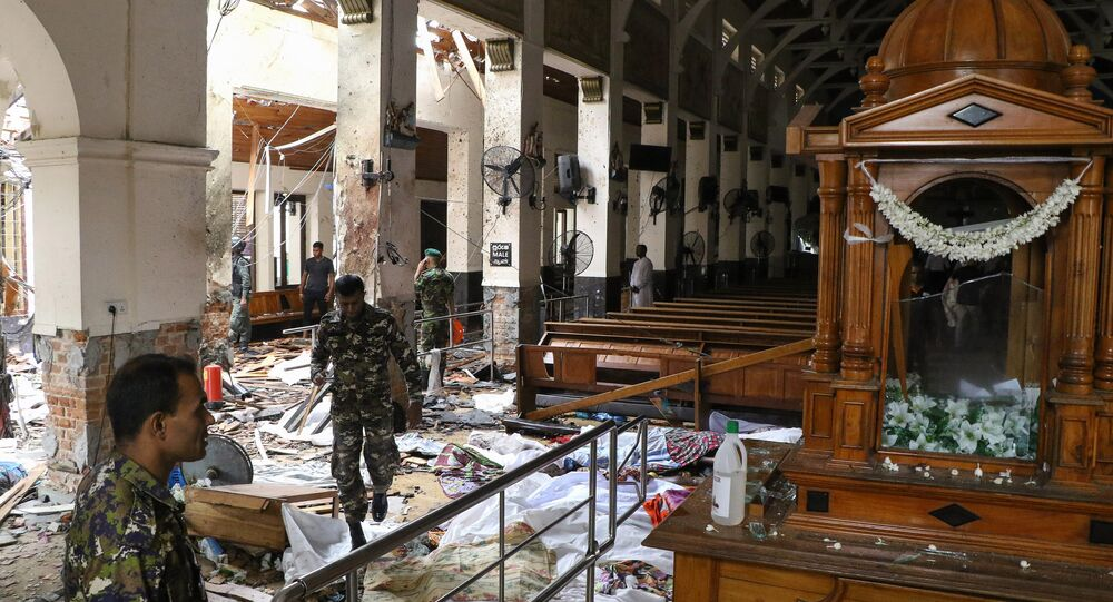 Sri Lankan security personnel walk past dead bodies covered with blankets amid blast debris at St. Anthony's Shrine following an explosion in the church in Kochchikade in Colombo on April 21, 2019.