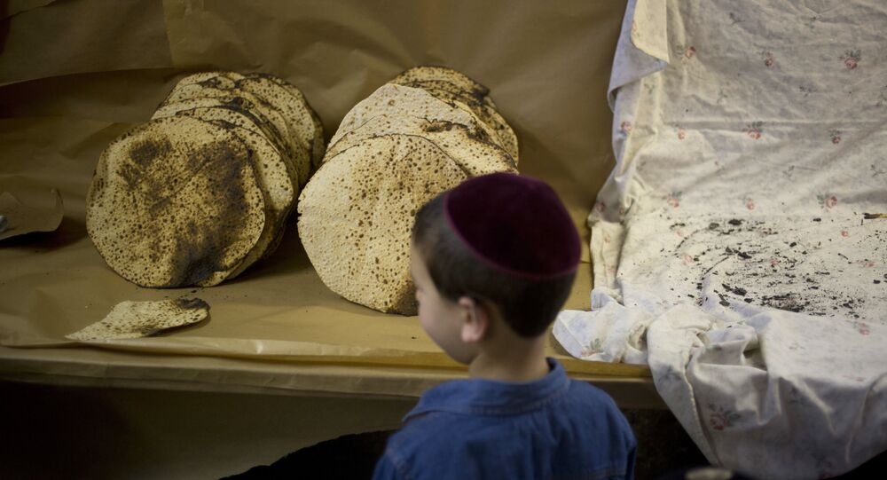 A boy looks at matzo, a traditional handmade Passover unleavened bread, that Jewish Orthodox bakers made in a bakery