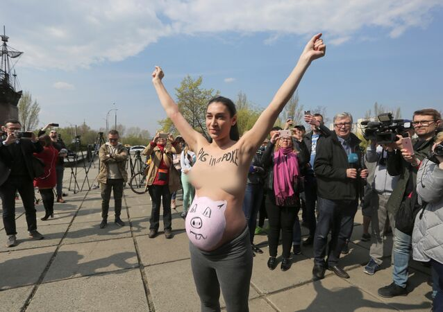 A topless activist of women's rights group Femen protests outside a polling station during the visit of Ukrainian presidential candidate Volodymyr Zelenskiy, who takes part in the second round of a presidential election in Kiev, Ukraine April 21, 2019.