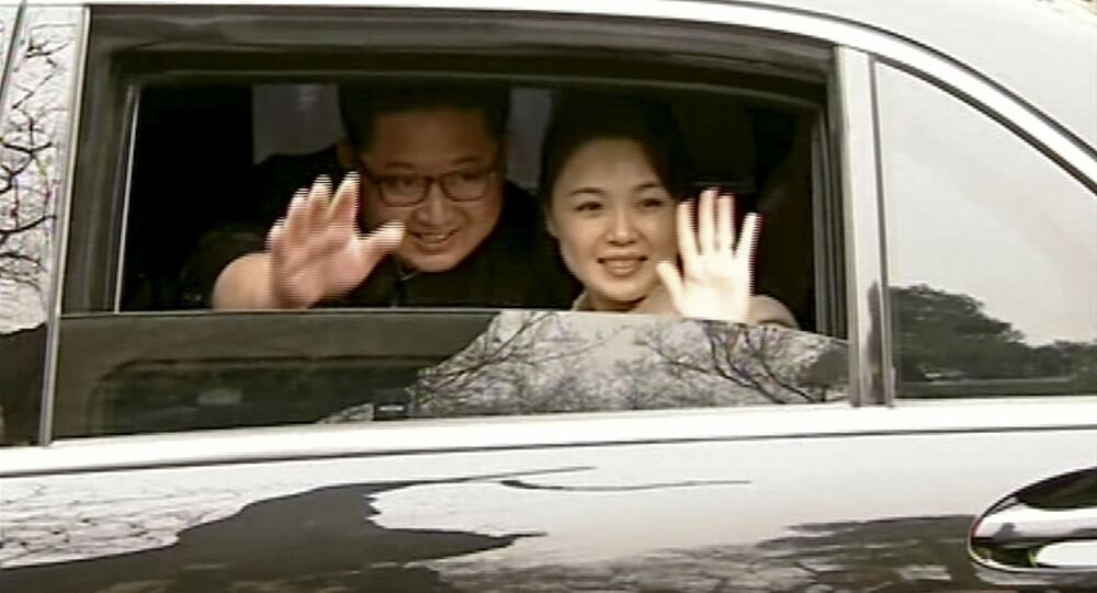 In this image taken from video footage run Wednesday, March 28, 2018, by China's CCTV via AP Video, North Korean leader Kim Jong Un, left, and his wife Ri Sol Ju wave from a car as they bid farewell to Chinese counterpart Xi Jinping and his wife Peng Liyuan in Beijing.