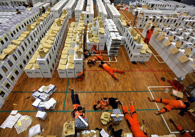 Workers lay during a break as they prepare election materials before their distribution to polling stations in a warehouse in Jakarta, Indonesia, April 15, 2019