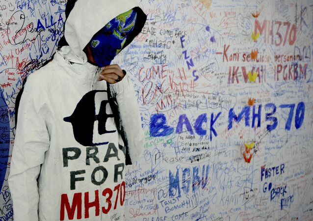 An unidentified woman wearing a mask depicting the flight of the missing Malaysia Airline, MH370, poses in front of the wall of hope at Kuala Lumpur International Airport in Sepang, Malaysia, Monday, March 17, 2014