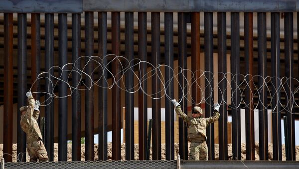U.S. soldiers install concertina wire next to the border fence between Mexico and the United States, in El Paso, Texas, U.S., in this picture taken from Ciudad Juarez, Mexico, April 4, 2019 - Sputnik International