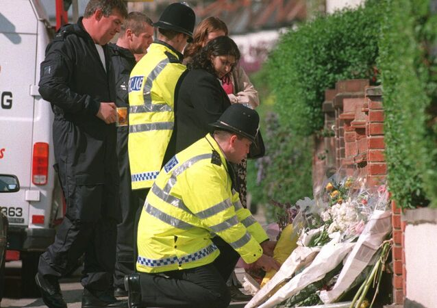A police officer lays a floral tribute to murdered TV presenter Jill Dando at her home in London where she was murdered in April 1999