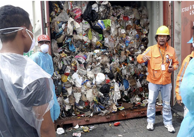 Philippine environment officials open one of the container vans containing garbage shipped illegally from Canada