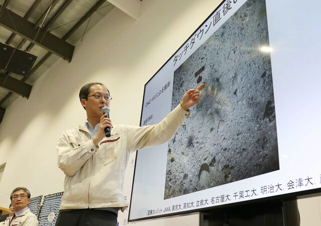 Yuichi Tsuda, project engineer of the Hayabusa2 mission from the Japan Aerospace Exploration Agency (JAXA) points at an image showing the surface of the asteroid Ryugu before touchdown by the Hayabusa2 spacecraft during a press conference in Sagamihara on February 22, 2019