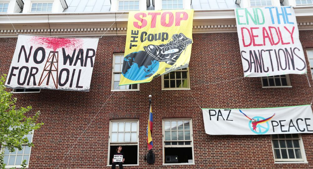 An activist in opposition of the U.S. involvement in Venezuela occupying the Venezuelan Embassy, sits in a window sill in Washington