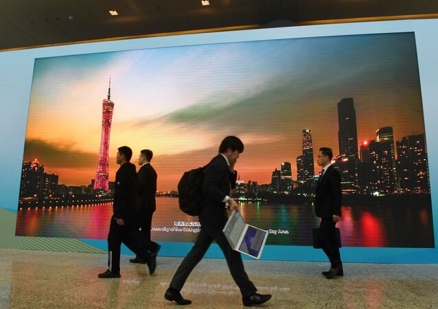 Journalists and officials walk past a screen showing a photo of the southern Chinese city of Guangzhou, at the venue of the Belt and Road Forum in Beijing on 26 April, 2019