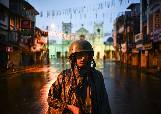 A Sri Lankan soldier stands guard under the rain at St. Anthony's Shrine in Colombo on April 25, 2019, following a series of bomb blasts targeting churches and luxury hotels on the Easter Sunday in Sri Lanka