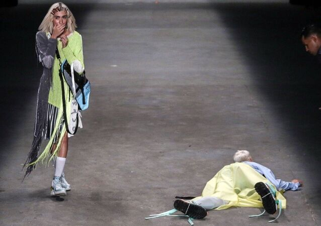 Model Tales Soares lies on the catwalk after he collapsed during Sao Paulo Fashion Week in Sao Paulo, Brazil, Saturday, April 27, 2019