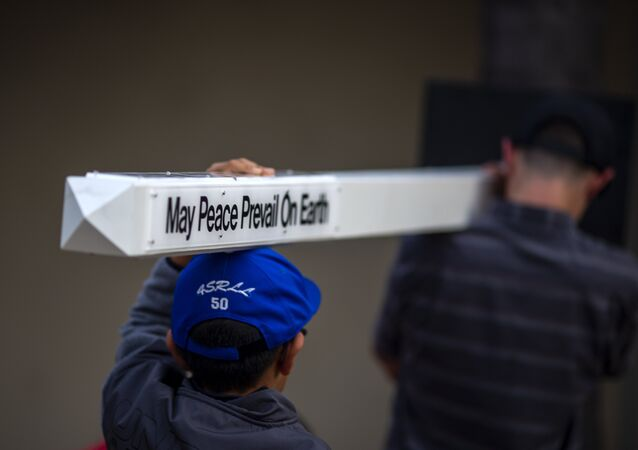 Boys carry a peace pole to an interfaith prayer and candlelight vigil at Rancho Bernardo Community Presbyterian Church on April 27, 2019 in Poway, California.