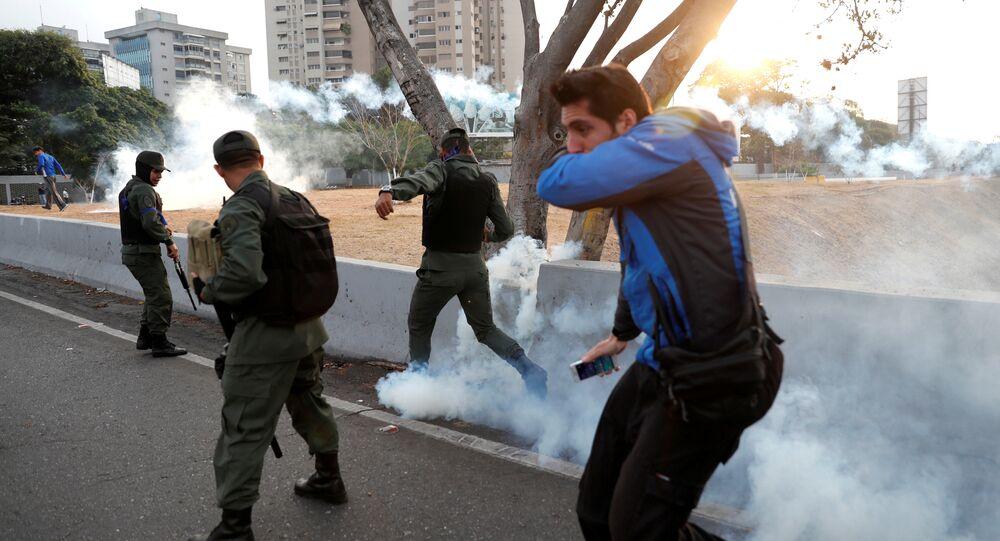 Military members react to tear gas, near the Generalisimo Francisco de Miranda Airbase La Carlota, in Caracas, Venezuela April 30, 2019