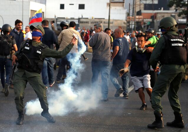 A military member throws a tear gas canister near the Generalisimo Francisco de Miranda Airbase La Carlota, in Caracas, Venezuela April 30, 2019