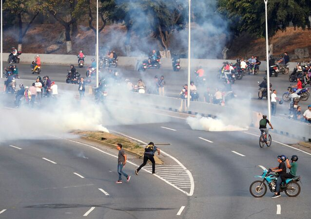 People react to tear gas near the Generalisimo Francisco de Miranda Airbase La Carlota, in Caracas, Venezuela April 30, 2019