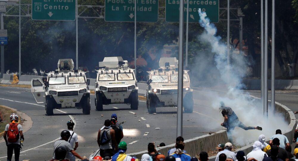 Opposition demonstrators face military vehicles near the Generalisimo Francisco de Miranda Airbase La Carlota in Caracas