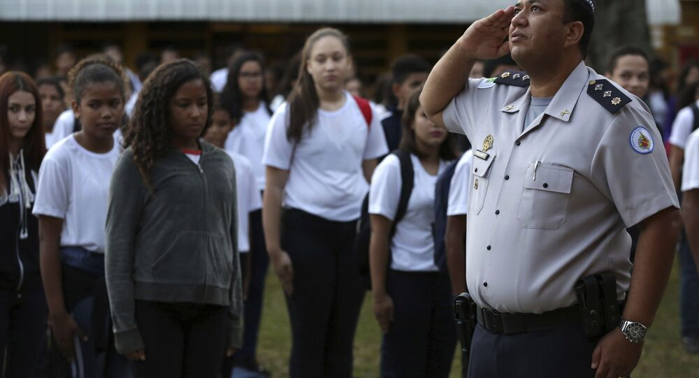 In this March 28, 2019 photo, Major Edney Freire salutes the flag during a ceremony in the main courtyard of the Ceilandia state school No. 7 in Brasilia, Brazil
