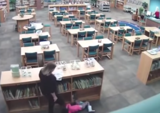 US teacher caught on surveillance footage kicking a student in the back after yanking them from a bookshelf.