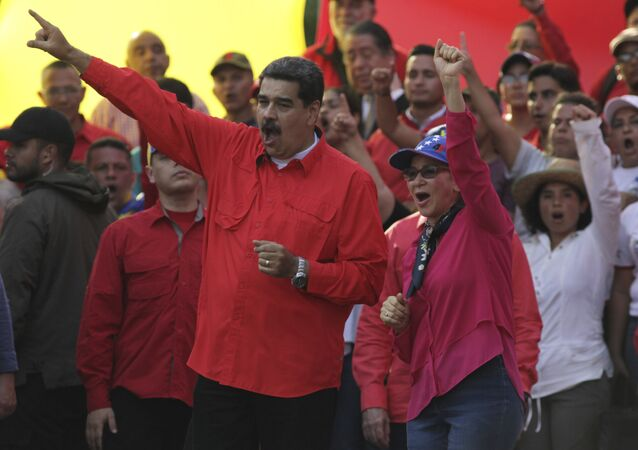 Venezuela's President Nicolas Maduro, center left, and his wife Cilia Flores, center right, wave at supporters during a rally in Caracas, Venezuela, Wednesday, May 1, 2019. Opposition leader Juan Guaidó called for Venezuelans to fill streets around the country Wednesday to demand President Nicolás Maduro's ouster. Maduro is also calling for his supporters to rally.