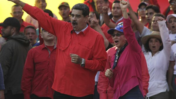 Venezuela's President Nicolas Maduro, center left, and his wife Cilia Flores, center right, wave at supporters during a rally in Caracas, Venezuela, Wednesday, May 1, 2019. Opposition leader Juan Guaidó called for Venezuelans to fill streets around the country Wednesday to demand President Nicolás Maduro's ouster. Maduro is also calling for his supporters to rally. - Sputnik International