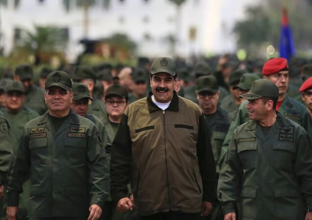 In this handout photo released by Miraflores Press Office, Venezuela's President Nicolas Maduro, center, accompanied by Defense Minister Gen. Vladimir Padrino Lopez, left, and the Strategies Operations Commander, Adm. Remigio Ceballos, arrive for a meeting with the troops at Fort Tiuna in Caracas, Venezuela, Thursday, May 2, 2019