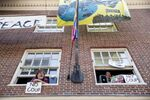 Pro Nicolas Maduro supporters look out the windows of the Venezuelan Embassy in Washington, Thursday, May 2, 2019. Pro interim government opposition leader Juan Guaido supporters have blocked the entrances to the embassy, cutting off supplies to pro Nicolas Maduro supporters occupying the building.