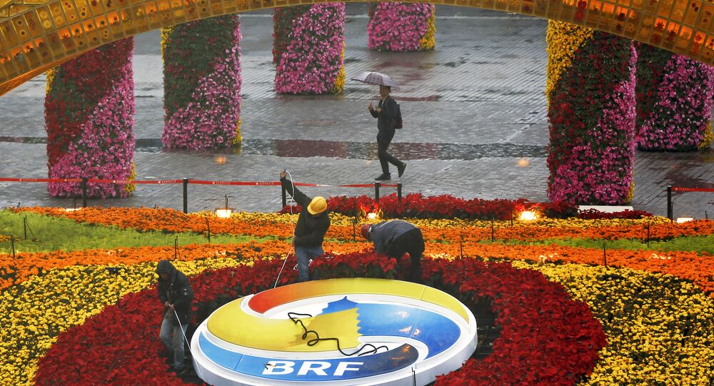 A man carrying an umbrella to shield from the rain as workers dismantle the Belt and Road Forum logo outside the media center as leaders are attending the round table summit of the Belt and Road Forum chaired by Chinese President Xi Jinping in Beijing, Saturday, April 27, 2019
