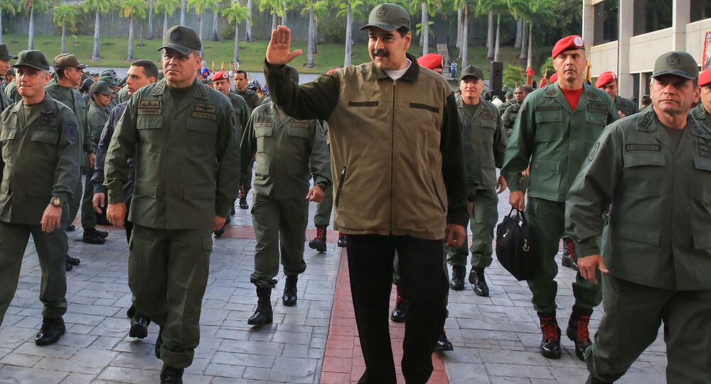 Venezuela's President Nicolas Maduro waves as he walks next to Venezuela's Defense Minister Vladimir Padrino Lopez and Remigio Ceballos, Strategic Operational Commander of the Bolivarian National Armed Forces, during a ceremony at a military base in Caracas, Venezuela May 2, 2019