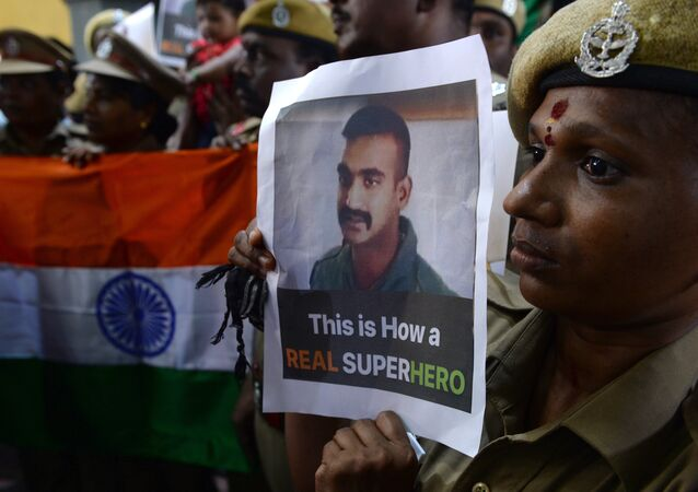 Indian security forces pose with the national flag and pictures of Indian Air Force pilot Abhinandan Varthaman during an event to pray for his return, at Kalikambal temple in Chennai on March 1, 2019.