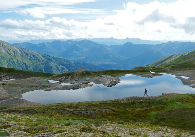 A hiker makes his way past an alpine pond on the Juneau ridge in Juneau, Alaska