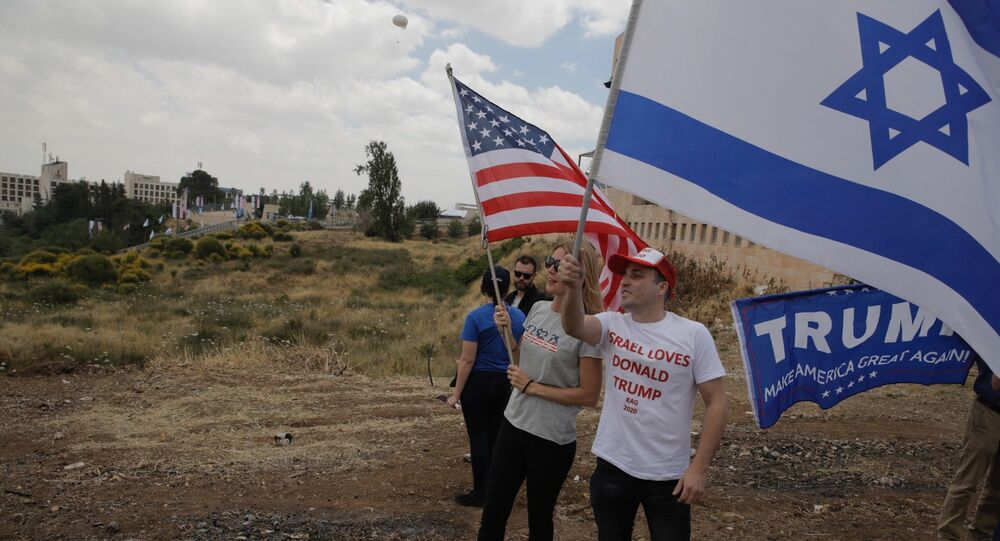 sraelis hold American and Israeli flags with the new U.S. embassy in the background in Jerusalem, Monday, May 14, 2018