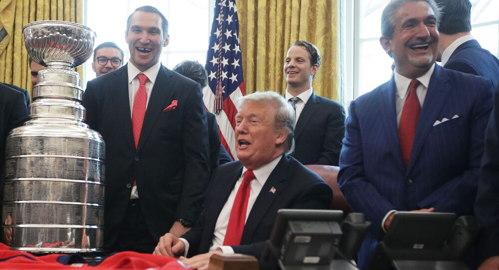 U.S. President Donald Trump shares a moment with left wing and MVP Alexander Ovechkin of the Washington Capitals, defenseman John Carlson, and team owner Ted Leonsis during an Oval Office event at the White House March 25, 2019 in Washington, DC