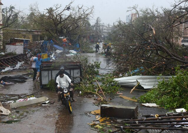 People move through debris on a road after Cyclone Fani hit Puri, in the eastern state of Odisha, India, May 3, 2019