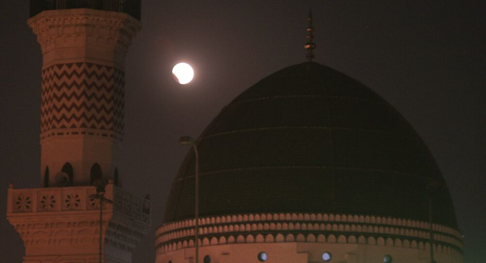 A lunar eclipse is seen in the sky beside th famous Sufi shrine, Data Darbar in Lahore, Pakistan (File)