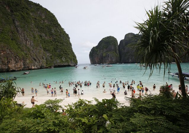 In this May 31, 2018, file photo, tourists walk the beach of Maya Bay, Phi Phi Leh island in Krabi province, Thailand.