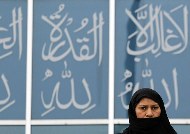 Backdropped by verses of the Quran, a worshipper from the Ahmadiyya Muslim community leaves Baitul Futuh Mosque in south London, after attending Friday prayers, Feb. 18, 2011