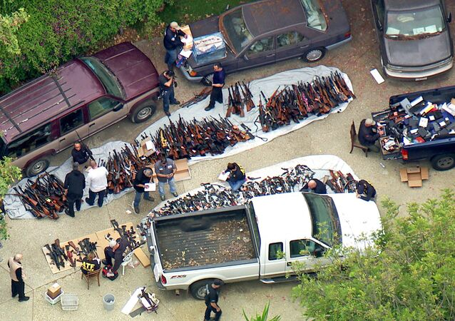 Investigators from the U.S. Bureau of Alcohol, Tobacco, Firearms and Explosives and police seize weapons from a home in the affluent Holmby Hills area of Los Angeles