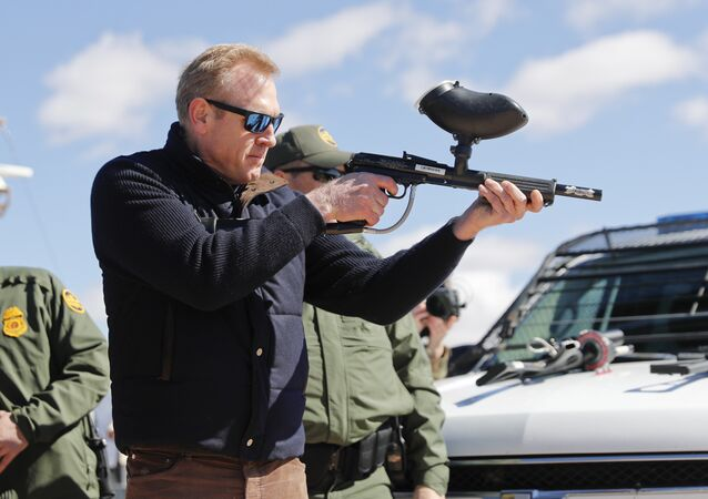 In this Feb. 23, 2019, photo, acting Secretary of Defense Patrick Shanahan, center, fires a modified painted ball gun that shoots pepper balls during a tour of the US-Mexico border at Santa Teresa Station in Sunland Park, N.M., Saturday, Feb. 23, 2019. Shanahan, the former Boeing executive, was in a familiar place, aboard an airplane, when he got word of a bolt-from-the-blue political shot across his bow. A key senator seemed to have buried Shanahan's chances of being nominated as the next secretary of defense. The crisis passed, but it highlighted the precarious position Shanahan occupies as he waits for President Donald Trump to decide who he will successor to Jim Mattis as leader of the Pentagon. (AP Photo/Pablo Martinez Monsivais)