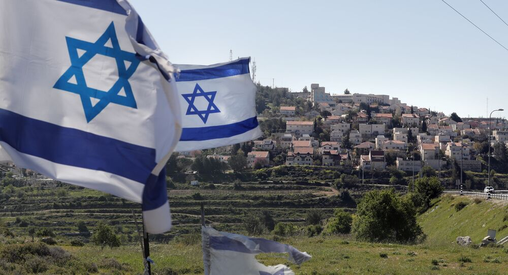 A photo taken on April 12, 2019 shows Israeli flags in front of a partial view of the Israeli settlement of Efrat situated on the southern outskirts of the West Bank city of Bethlehem